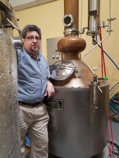 Owner and distiller Derrick Mancini kicking off the distillery tour next to his still.